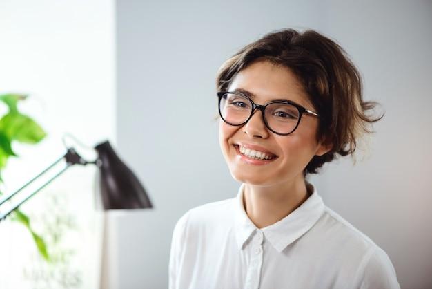 Portret Młody Piękny Bizneswoman Ono Uśmiecha Się Przy Miejscem Pracy W Biurze. Darmowe Zdjęcia