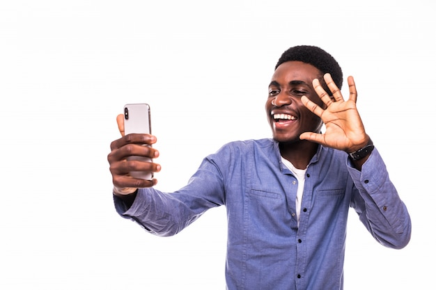 Portret Młody Przystojny Amerykanina Afrykańskiego Pochodzenia Mężczyzna Używa Smartphone Brać Selfie Obrazki I Uśmiechniętą Pozycję Przeciw Biel ścianie Darmowe Zdjęcia