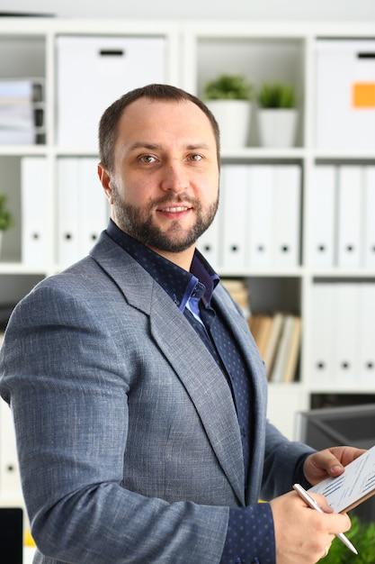 Portret Młody Przystojny Obiecujący Biznesmen W Biurze Premium Zdjęcia