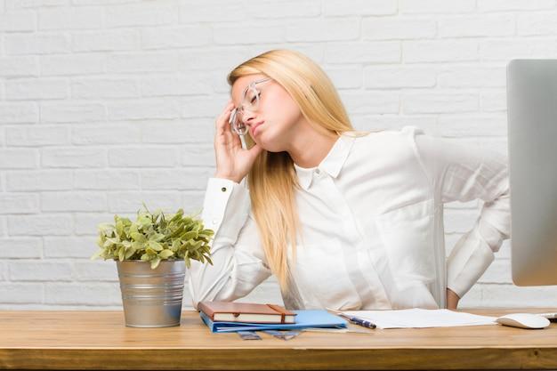 Portret młody studencki obsiadanie na jej biurku robi zadaniom z bólem pleców z powodu praca stresu Premium Zdjęcia
