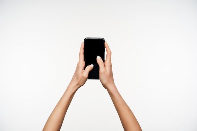 Portret Młodych, Jasnoskórych, ładnych Dłoni Trzymających Czarny Nowoczesny Smartfon, Pozując Na Biało I Trzymając Kciuki Na Ekranie Darmowe Zdjęcia