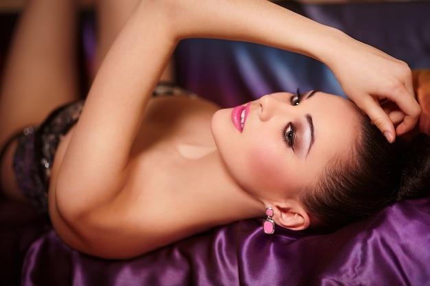Portret Moda Model Piękna Brunetka Dziewczyna Z Jasnym Makijażu Różowe Usta I Fryzurę Jasne Kolorowe Leżące Na łóżku Darmowe Zdjęcia