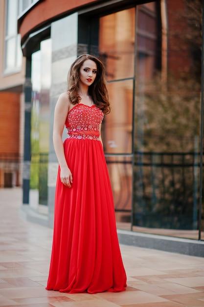 Portret modna dziewczyna przy czerwoną wieczór suknią pozuje tła lustra okno nowożytny budynek Premium Zdjęcia