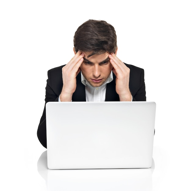 Portret Myślenia Pracownik Biurowy Z Laptopem O Stres, Siedząc Na Stole, Na Białym Tle. Darmowe Zdjęcia