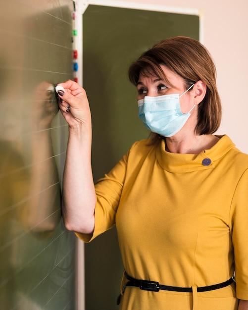 Portret Nauczyciela Z Maską Pisania Na Tablicy Darmowe Zdjęcia