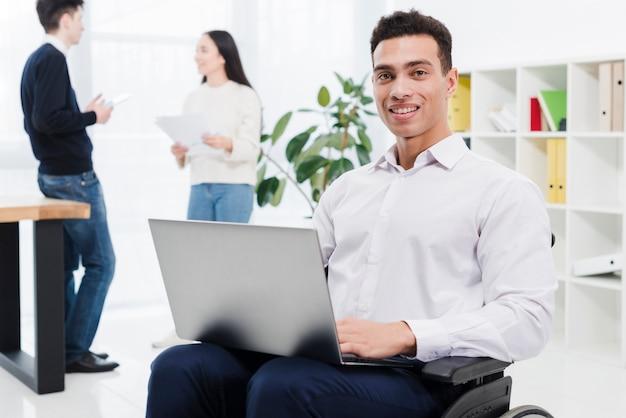 Portret niepełnosprawny uśmiechnięty młody biznesmen siedzi na wózku inwalidzkim z laptopem i współpracownikiem w tle Darmowe Zdjęcia