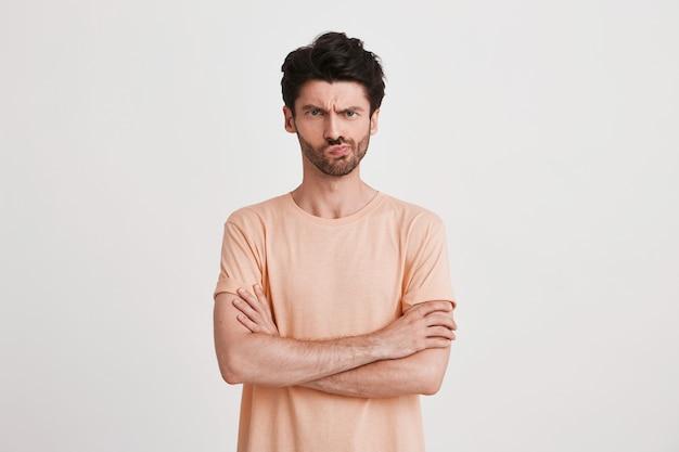 Portret Niezadowolonego, Niezadowolonego Młodzieńca Z Włosiem Nosi Brzoskwiniową Koszulkę, Wygląda Na Zdenerwowanego I Wskazuje Na Bok Palcem Odizolowanym Na Białym Darmowe Zdjęcia