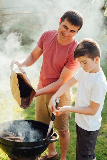 Portret ojca i syna zapalając węgle w grillu Darmowe Zdjęcia