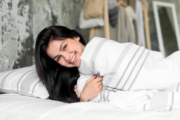 Portret Ono Uśmiecha Się W łóżku Młoda Kobieta Darmowe Zdjęcia