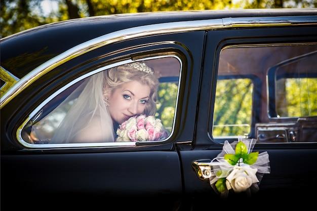 Portret panny młodej w oknie ślubnego samochodu retro Premium Zdjęcia