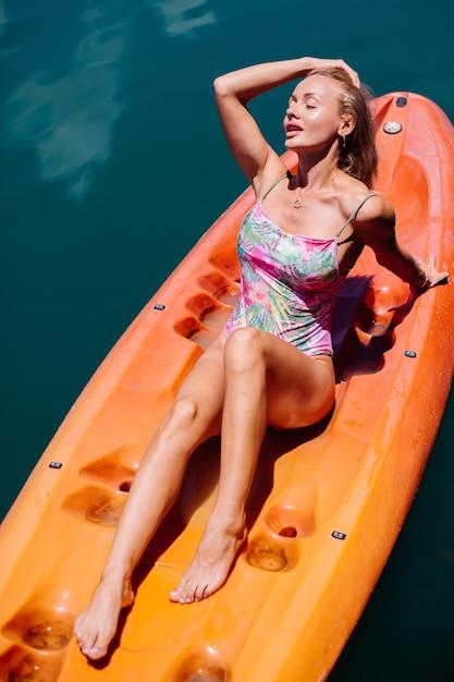 Portret Pasuje Młody Turysta Kaukaski Kobieta W Bikini Relaks Na Kajaku Nad Pięknym Jeziorem W Tajlandii. Kobieta Na Wakacjach, Ciesząc Się Słonecznym Dniem. Darmowe Zdjęcia