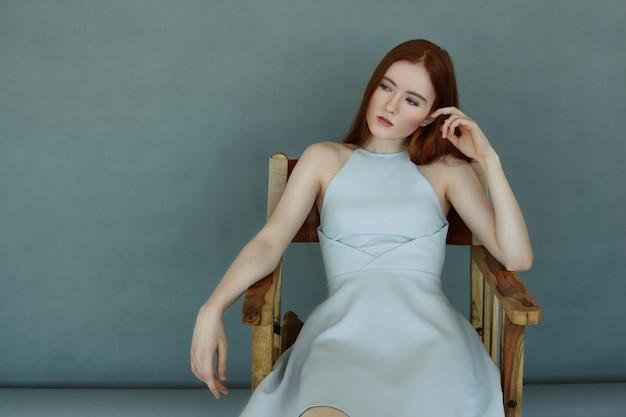 Portret Pewnej Rudowłosej Dziewczyny, Która Ma Spojrzenie Na ścianę Przestrzeni Kopii, Siedząc Na Krześle. Wspaniała Modelka Na Sobie Niebieską Sukienkę, Odpoczynek I Pozowanie Darmowe Zdjęcia