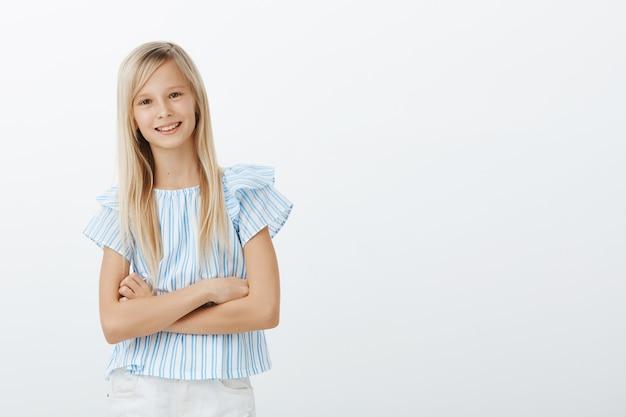 Portret Pewnej Siebie, Uroczej Europejskiej Dziewczyny W Niebieskiej Bluzce, Trzymającej Ręce Skrzyżowane Na Piersi I Uśmiechającej Się Z Pewnym Siebie Wyrazem, Energicznej I Radosnej Darmowe Zdjęcia