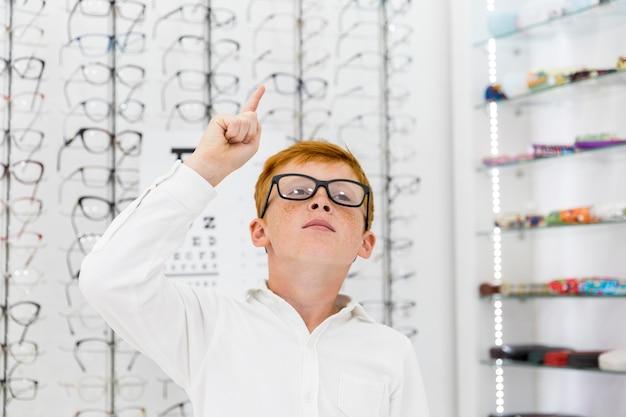 Portret Piega Chłopiec Wskazuje W Górę Kierunku W Optyka Sklepie Darmowe Zdjęcia