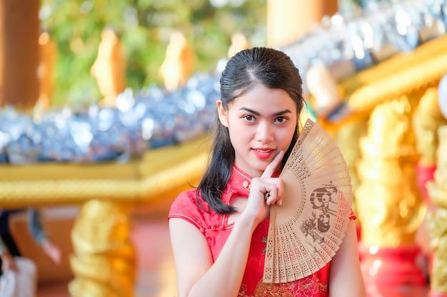 Portret Piękna Azjatycka Dziewczyna Jest Ubranym Cheongsam Czerwieni Suknię Trzyma Fan Premium Zdjęcia