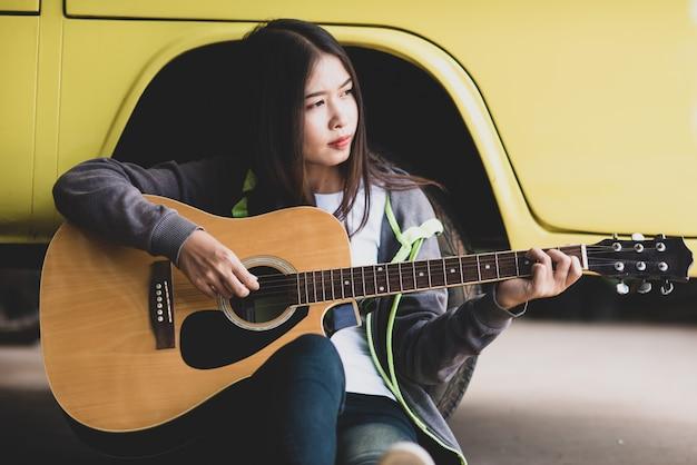 Portret piękna azjatycka kobieta trzyma gitarę akustyczną Darmowe Zdjęcia
