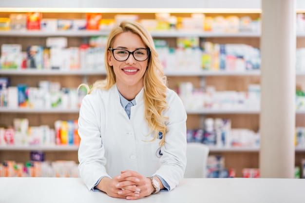 Portret Piękna Blondynki Farmaceuta Opiera Na Kontuarze Przy Farmaceutycznym Sklepem. Premium Zdjęcia