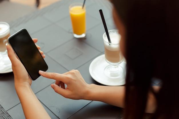Portret Piękna Dziewczyna Używa Jej Telefon Komórkowego W Kawiarni Premium Zdjęcia