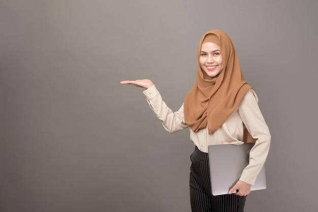 Portret Piękna Kobieta Z Hijab Trzyma Komputerowego Laptop Na Szarość Premium Zdjęcia