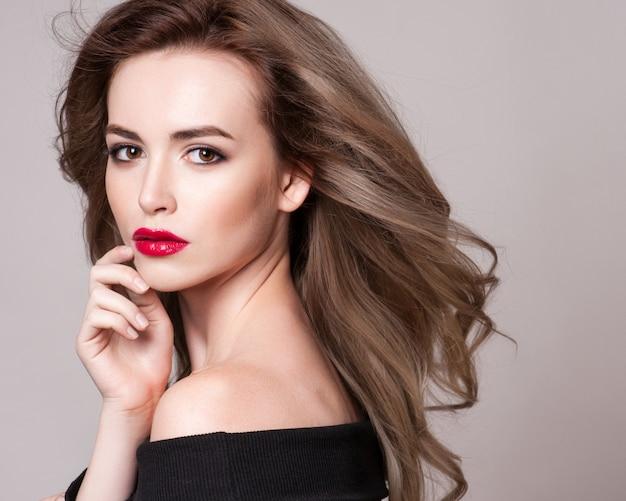 Portret piękna kobieta z kędzierzawą fryzurą i jaskrawym makeup Premium Zdjęcia