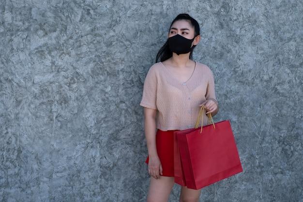 Portret Piękna Młoda Azja Kobieta Jest Ubranym Maskę Z Mień Torba Na Zakupy Przy Betonową ścianą Premium Zdjęcia