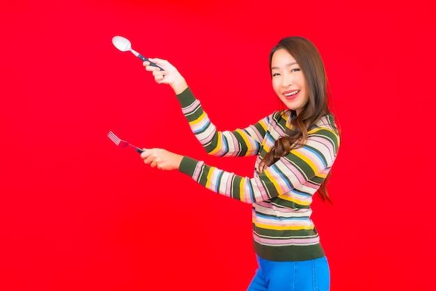 Portret Piękna Młoda Azjatycka Kobieta Gotowa Do Jedzenia Z łyżką I Widelcem Na Czerwonej ścianie Darmowe Zdjęcia