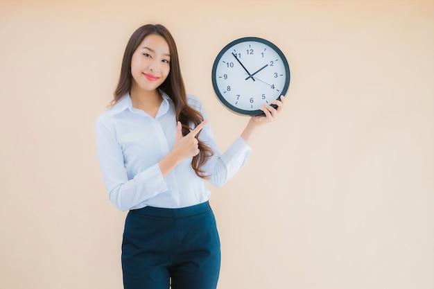 Portret Piękna Młoda Azjatycka Kobieta Pokazuje Budzik Lub Zegar Darmowe Zdjęcia