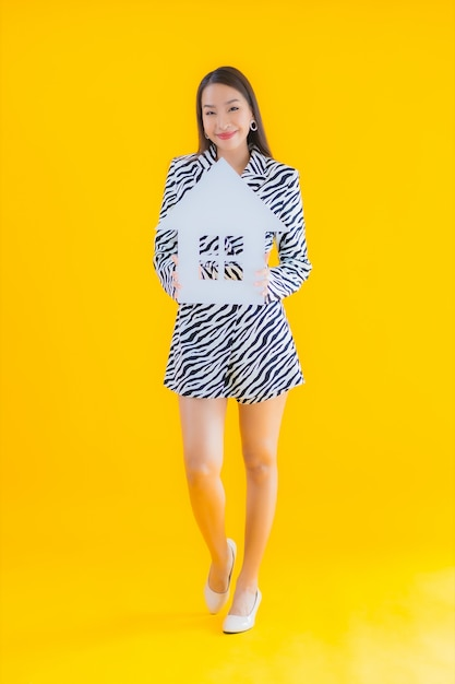 Portret Piękna Młoda Azjatycka Kobieta Pokazuje Znak Domu Lub Domu Na żółto Darmowe Zdjęcia