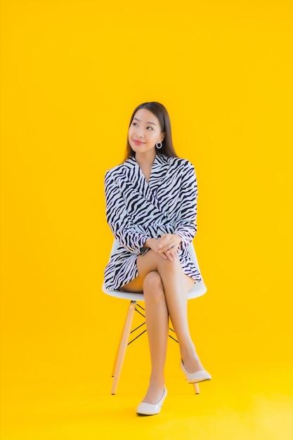 Portret Piękna Młoda Azjatycka Kobieta Siedzi Na Krześle Z Akcją Na żółto Darmowe Zdjęcia