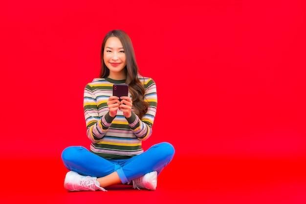 Portret Piękna Młoda Azjatycka Kobieta Używa Inteligentnego Telefonu Komórkowego Na Czerwonej ścianie Na Białym Tle Darmowe Zdjęcia