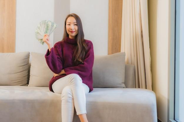 Portret Piękna Młoda Azjatycka Kobieta Z Dużą Ilością Gotówki I Pieniędzy Na Kanapie We Wnętrzu Salonu Darmowe Zdjęcia