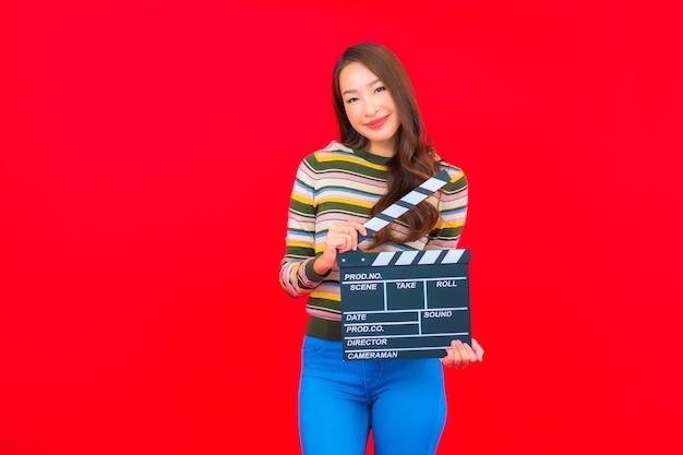 Portret Piękna Młoda Azjatycka Kobieta Z Filmu łupków Cięcia Na Czerwonej ścianie Na Białym Tle Darmowe Zdjęcia