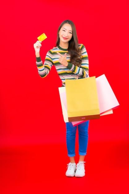 Portret Piękna Młoda Azjatycka Kobieta Z Kolorową Torbą Na Zakupy I Kartą Kredytową Na Czerwonej ścianie Darmowe Zdjęcia