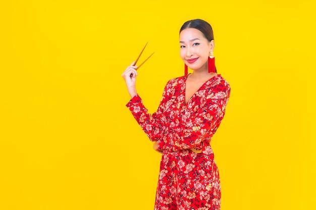 Portret Piękna Młoda Azjatycka Kobieta Z Pałeczkami Na Kolor Na Białym Tle ściany Darmowe Zdjęcia