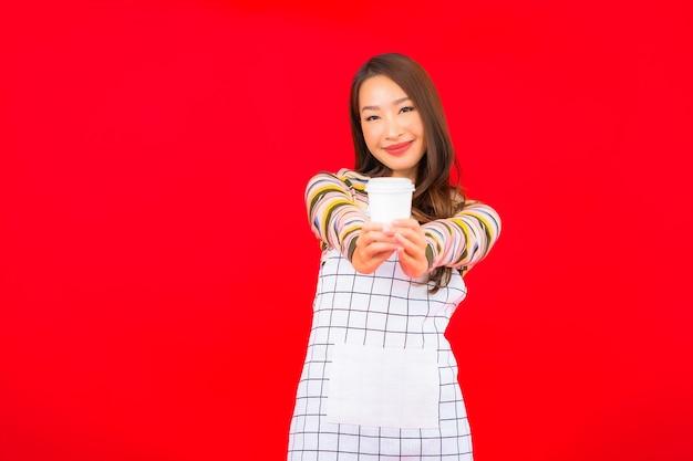 Portret Piękna Młoda Azjatykcia Kobieta Nosić Fartuch Z Filiżanką Kawy Na Czerwonej ścianie Darmowe Zdjęcia