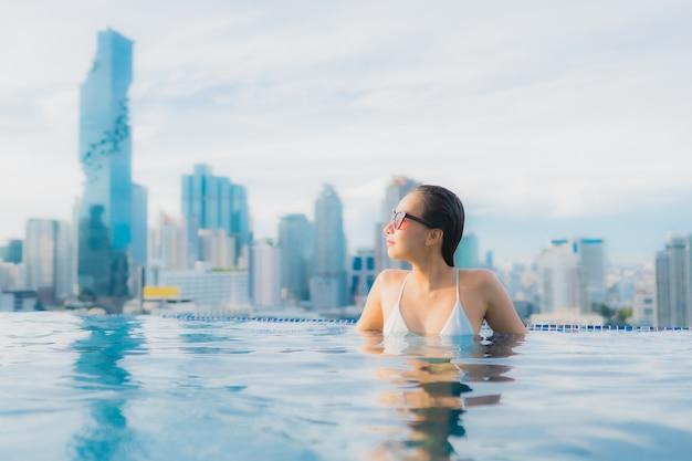Portret Piękna Młoda Azjatykcia Kobieta Relaksuje Szczęśliwego Uśmiechu Czas Wolnego Wokoło Plenerowego Pływackiego Basenu Darmowe Zdjęcia