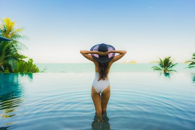 Portret piękna młoda azjatykcia kobieta relaksuje w luksusowym plenerowym pływackim basenie w hotelowego kurortu prawie plażowym dennym oceanie Darmowe Zdjęcia