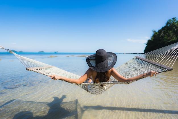 Portret Piękna Młoda Azjatykcia Kobieta Siedzi Na Hamaku Wokoło Dennej Plaży Oceanu Dla Relaksu Darmowe Zdjęcia