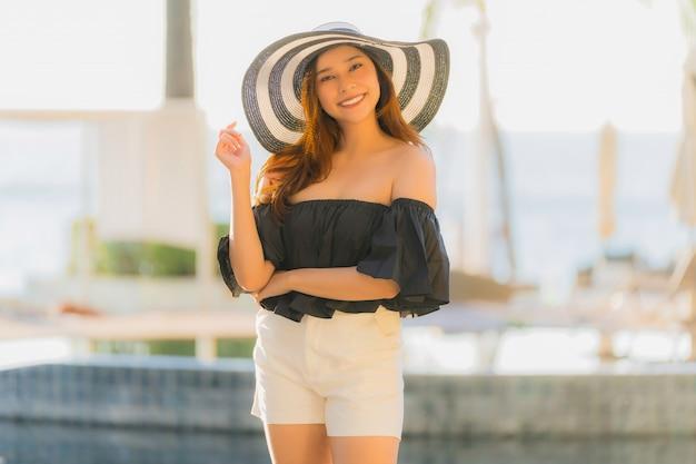 Portret Piękna Młoda Azjatykcia Kobieta Szczęśliwa I Uśmiech Z Podróżą W Hotelowego Kurortu Neary Morzu I Plaży Darmowe Zdjęcia