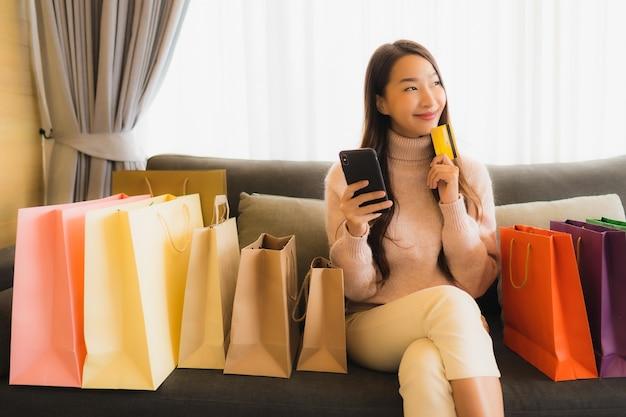 Portret Piękna Młoda Azjatykcia Kobieta Używa Laptop Lub Mądrze Mobilnego Telefon Komórkowego Dla Robić Zakupy Online Na Kanapie Wokoło Torba Na Zakupy Darmowe Zdjęcia