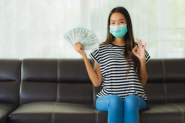 Portret Piękna Młoda Azjatykcia Kobieta Z Maską Na Kanapie Pokazuje Pieniądze Darmowe Zdjęcia