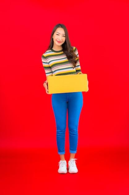 Portret Piękna Młoda Azjatykcia Kobieta Z Paczką Na Czerwonej ścianie Na Białym Tle Darmowe Zdjęcia