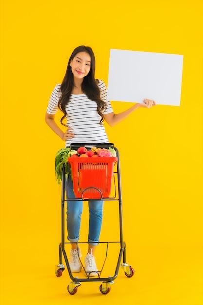Portret Piękna Młoda Azjatykcia Kobieta Z Sklep Spożywczy Koszykową Furą I Pokazuje Bielowi Pustą Deskę Darmowe Zdjęcia
