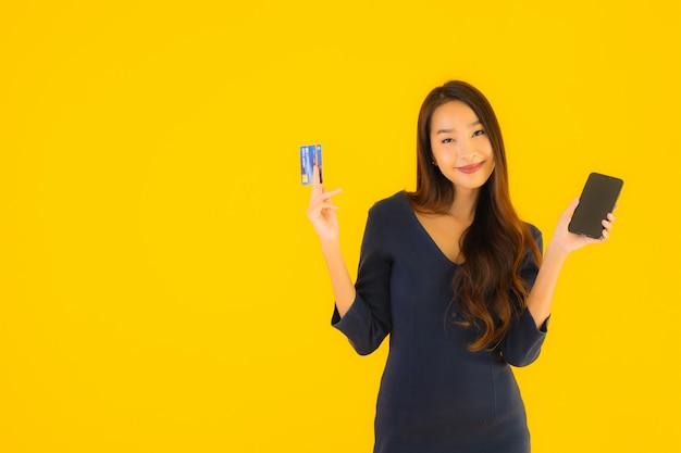 Portret Piękna Młoda Azjatykcia Kobieta Z Telefonem I Kredytową Kartą Darmowe Zdjęcia