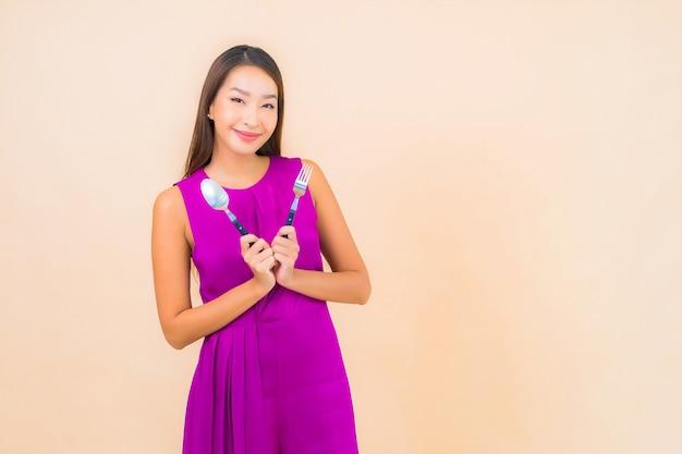 Portret Piękna Młoda Azjatykcia Kobieta Z Widelcem I łyżką Gotową Do Spożycia Na Kolorowym Tle Darmowe Zdjęcia