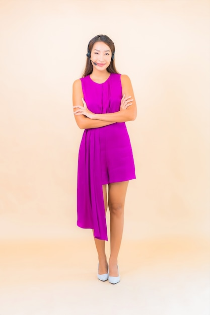 Portret Piękna Młoda Azjatykcia Kobieta Z Zestawem Słuchawkowym Dla Klienta Call Center Na Kolorowym Tle Darmowe Zdjęcia