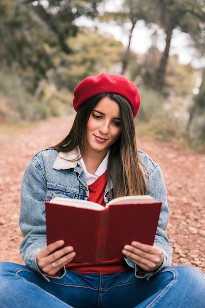 Portret piękna młoda kobieta czyta książkę przy outdoors Darmowe Zdjęcia