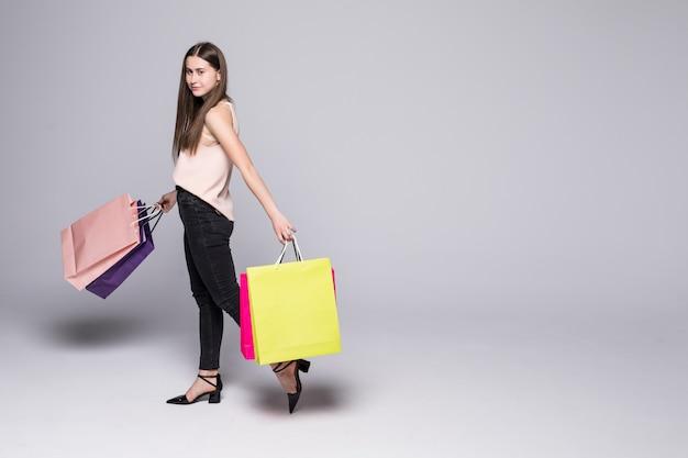 Portret Piękna Młoda Kobieta Pozuje Z Torba Na Zakupy Odizolowywającymi Na Biel ścianie Darmowe Zdjęcia