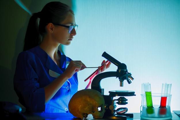 Portret Piękna Młoda Kobieta W Laboranckim Obsiadaniu Na Jej Miejscu Pracy. Premium Zdjęcia