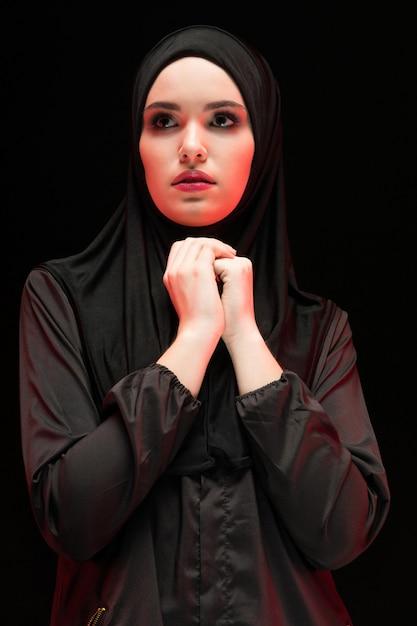 Portret Piękna Poważna Młoda Muzułmańska Kobieta Jest Ubranym Czarnego Hijab Z Rękami Blisko Ona Twarz Jak Modli Się Pojęcie Premium Zdjęcia